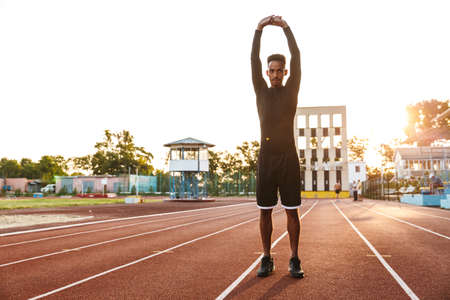 Image of athletic african american man stretching his body at sports stadium outdoors Zdjęcie Seryjne