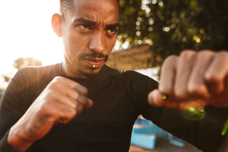 Image of muscular african american man clenching fists and boxing on sports ground outdoors