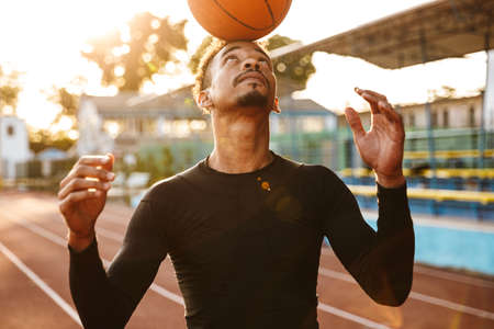 Image of a strong african handsome young sports man at stadium outdoors play basketball.