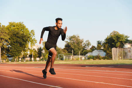 Image of athletic african american man running on sports stadium outdoors