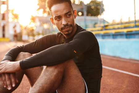 Image of focused african american man sitting at sports ground while doing workout outdoors Zdjęcie Seryjne