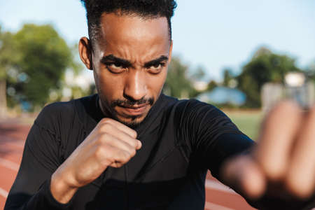 Image of focused african american man clenching fists and boxing on sports ground outdoors