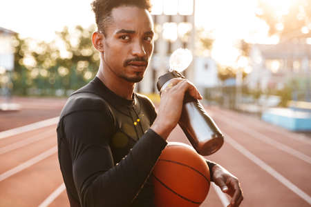 Image of a african handsome young sports man at stadium outdoors holding basketball drinking water.