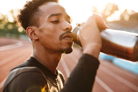 Image of a african serious handsome young sports man at stadium outdoors drinking water.