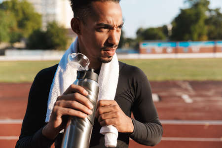Image of handsome african american man with towel drinking water on sports ground outdoors