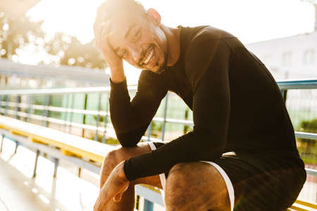 Image of happy african american man in sportswear sitting on bench at stadium outdoors in morning Zdjęcie Seryjne