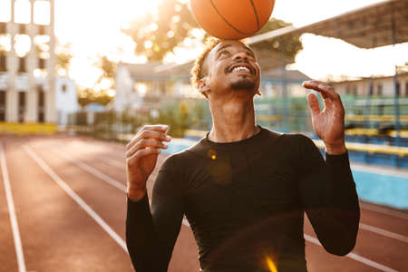 Photo of african cheerful happy strong young sports man at stadium outdoors play basketball.