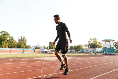 Image of active african american man in sportswear doing workout with jumping rope at stadium in morning outdoors Zdjęcie Seryjne