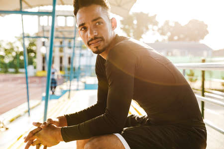 Image of handsome african american man in sportswear sitting on bench at stadium outdoors in morning