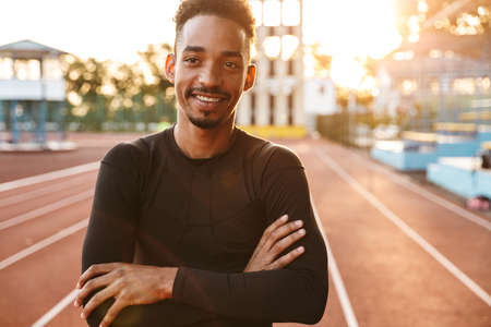 Image of smiling african american man standing at running track on sports ground outdoors