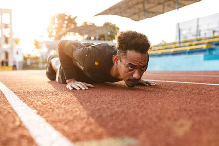 Image of strong african american man lying on sports stadium while doing workout outdoors