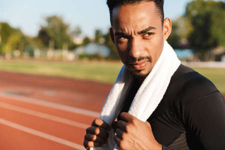 Image of athletic african american man standing at running track on sports ground with towel