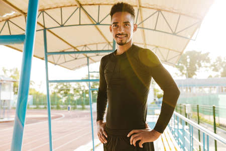 Image of happy african american man in sportswear smiling while doing workout at stadium outdoors in morning