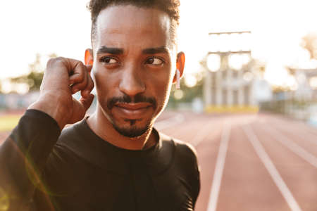 Image of a african concentrated serious handsome young sports man at stadium outdoors listening music with wireless  earphones. Zdjęcie Seryjne