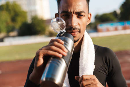 Image of athletic african american man with towel drinking water on sports ground outdoors