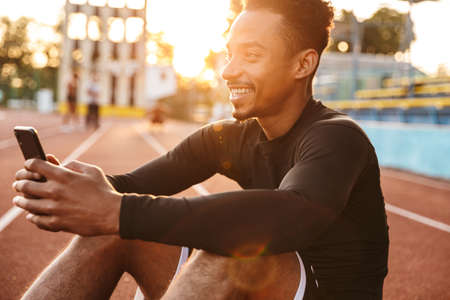 Image of happy african american man holding smartphone while sitting at sports ground outdoors Zdjęcie Seryjne