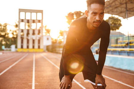 Image of tense african american man standing at running track on sports ground outdoors