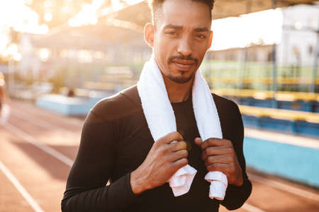 Image of handsome african american man standing at running track on sports ground with towel
