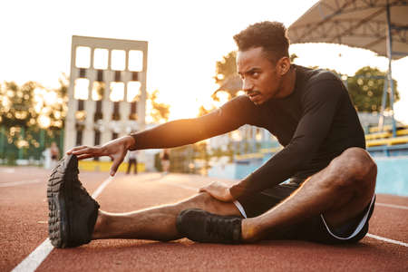 Image of strong african american man stretching his body while sitting at sports ground outdoors