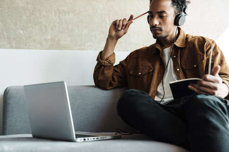 Photo of serious african american man using headphones while working with laptop in bright room
