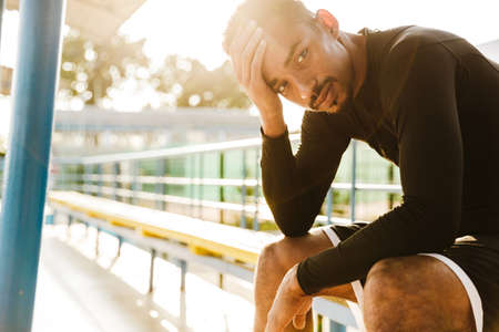 Image of athletic african american man in sportswear sitting on bench at stadium outdoors in morning