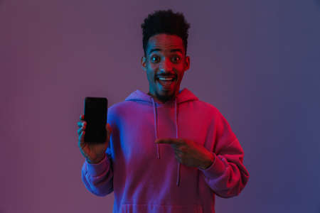 Portrait of happy african american man in colorful hoodie holding and pointing finger at cellphone isolated over violet background 免版税图像