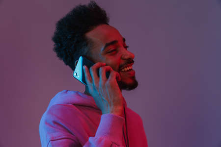 Portrait of unshaved african american man in colorful hoodie talking on cellphone isolated over violet background