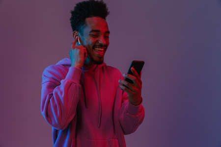 Portrait of joyful african american man in colorful hoodie talking on cellphone with earpod isolated over violet background