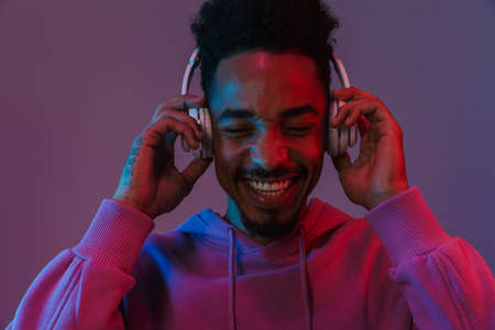 Portrait of joyful african american man in colorful hoodie listening to music with headphones isolated over violet background