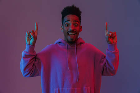 Portrait of exciting african american man in colorful hoodie looking at camera and pointing fingers upward isolated over violet background