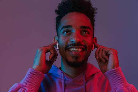Portrait of smiling african american man in colorful hoodie listening to music with earpods isolated over violet background