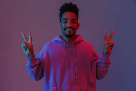 Portrait of satisfied african american man in colorful hoodie smiling and showing peace sing isolated over violet background 免版税图像