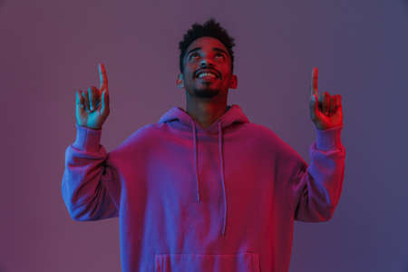 Portrait of positive african american man in colorful hoodie looking and pointing fingers upward isolated over violet background 免版税图像