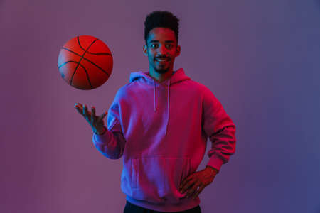 Portrait of masculine african american man in colorful hoodie poising at camera with basketball isolated over violet background