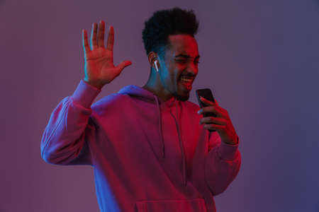 Portrait of handsome african american man in colorful hoodie listening to music on cellphone with earpod isolated over violet background