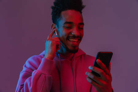 Portrait of pleased african american man in colorful hoodie talking on cellphone with earpod isolated over violet background