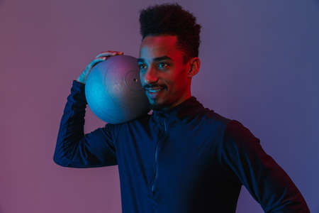 Portrait of satisfied african american man in sportswear poising at camera with fitball isolated over violet background 免版税图像