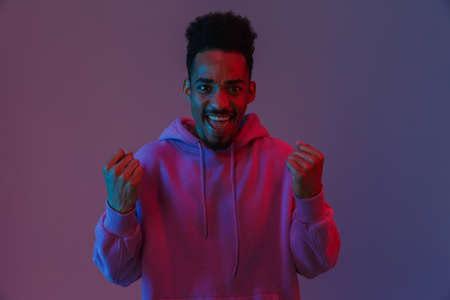 Portrait of happy african american man in colorful hoodie celebrating success isolated over violet background