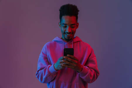 Portrait of happy african american man in colorful hoodie making video call on cellphone isolated over violet background