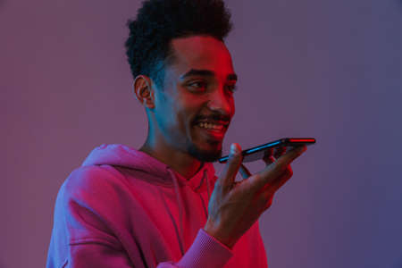 Portrait of pleased african american man in colorful hoodie talking on cellphone isolated over violet background 免版税图像