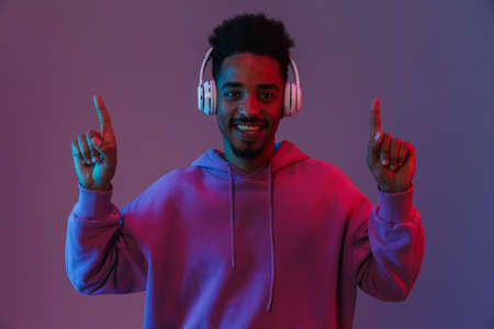 Portrait of joyful african american man listening to music with headphones and pointing fingers upward isolated over violet background