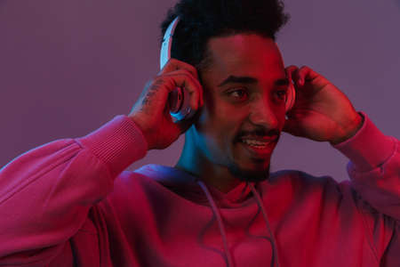 Portrait of unshaved african american man in colorful hoodie listening to music with headphones isolated over violet background