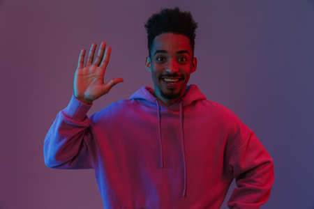 Portrait of relaxed african american man in colorful hoodie poising on camera with waving hand isolated over violet background