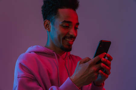 Portrait of young african american man in colorful hoodie making video call on cellphone isolated over violet background
