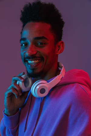 Portrait of happy african american man in colorful hoodie posing with headphones isolated over violet background