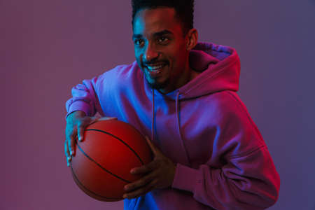 Portrait of happy african american man in colorful hoodie poising at camera with basketball isolated over violet background