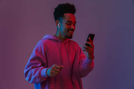 Portrait of handsome african american man in colorful hoodie talking on cellphone with earpod isolated over violet background