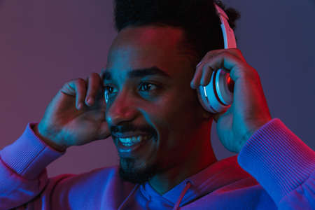 Portrait of handsome african american man in colorful hoodie listening to music with headphones isolated over violet background 免版税图像