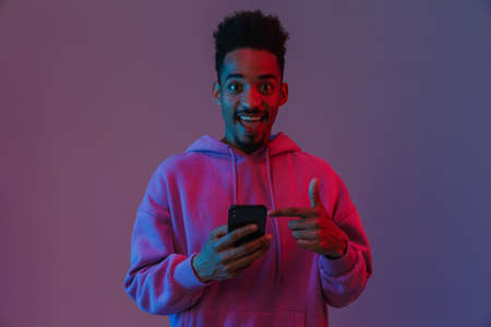Portrait of excited african american man in colorful hoodie holding and pointing finger at cellphone isolated over violet background