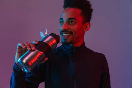 Portrait of smiling african american man in sportswear poising at camera with  bottle isolated over violet background 免版税图像